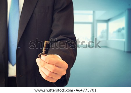 Businessman holding key in modern background