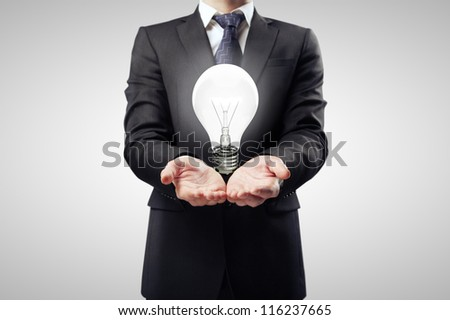 businessman holding lamp in hand - stock photo