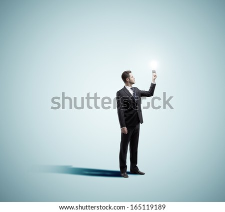 businessman holding lamp on a blue background - stock photo