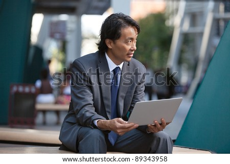 Businessman holding laptop and looking away - stock photo
