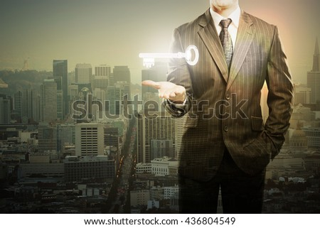 Businessman holding levitating key in city with setting sun. Double exposure