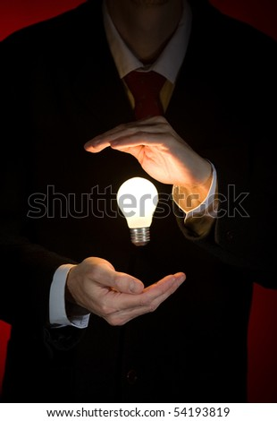 businessman holding light bulb - stock photo