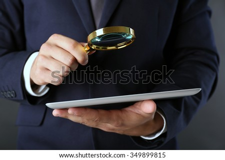Businessman holding magnifying glass and digital tablet on dark grey background, searching and examining concept - stock photo