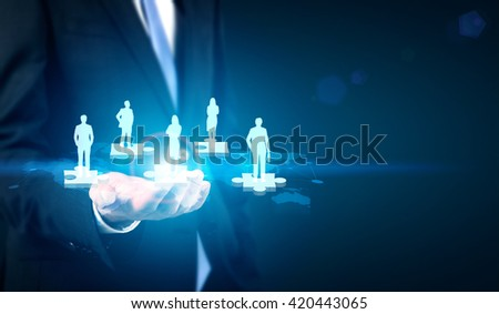 Businessman holding map with people icons on puzzle pieces. Concept of partnership and teamwork
