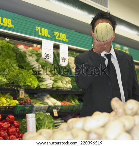 Businessman holding melon in front of his face in supermarket - stock photo