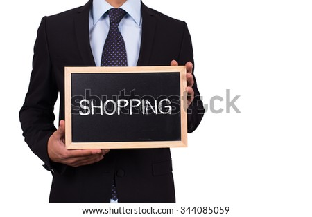 Businessman holding mini blackboard with SHOPPING message - stock photo