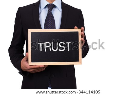 Businessman holding mini blackboard with TRUST message - stock photo