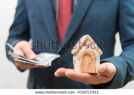 Businessman holding money with house model on hand - stock photo