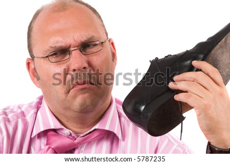Businessman holding one of his shoes close to his nose pulling a face