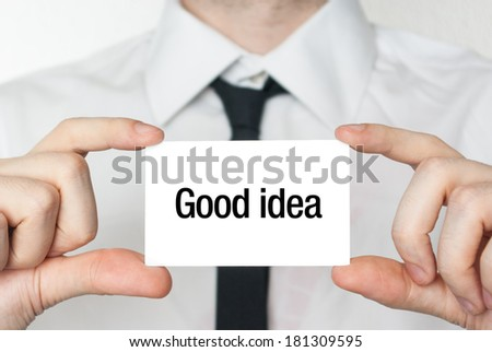 Businessman holding or showing a card with text Good idea - stock photo