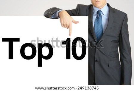 Businessman holding or showing banner with text top 10 - stock photo