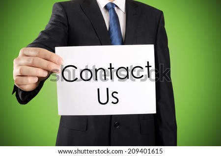Businessman holding or showing card with Contact Us text  - stock photo