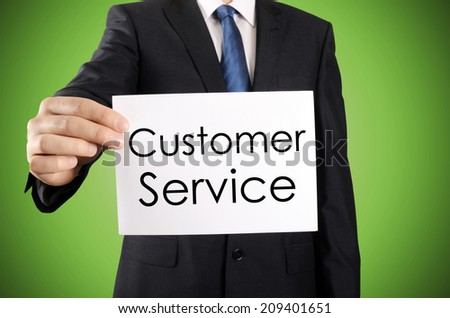 Businessman holding or showing card with Customer Service text  - stock photo