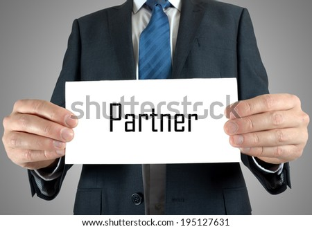 Businessman holding or showing card with partner word - stock photo