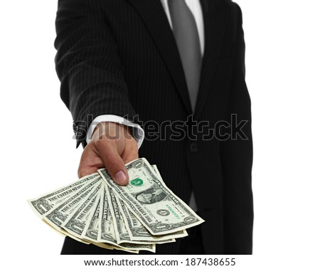 Businessman holding out cash in front of him - stock photo