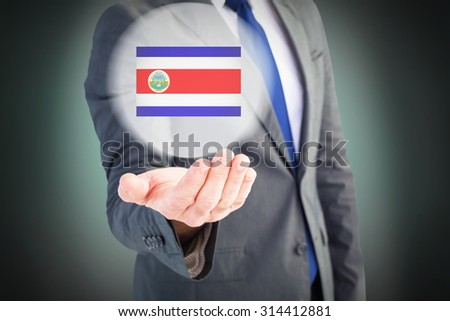 Businessman holding out his hand against green background with vignette