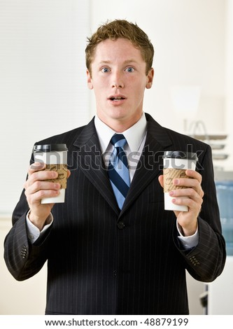 Businessman holding paper coffee cups - stock photo