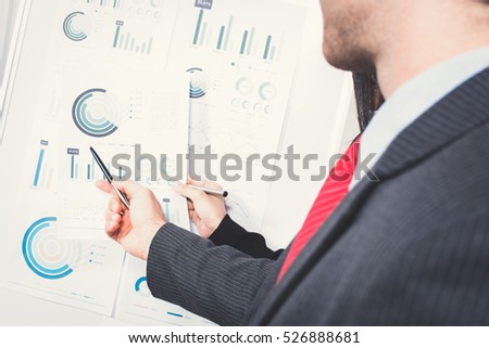 Businessman holding pen and pointing to graph on the paper