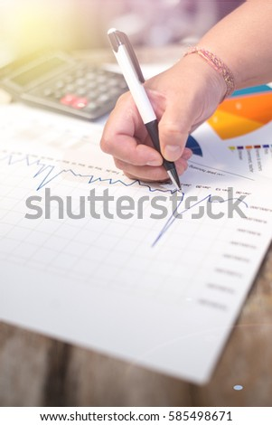 Businessman holding pen and think with cost with calculator
