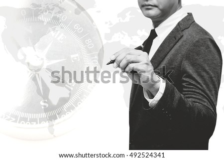 businessman holding pen with world map double exposure with compass with black and white filter