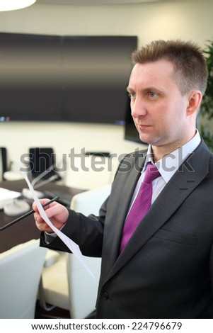 Businessman holding piece of paper and pencil in office - stock photo