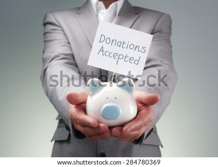 Businessman holding piggy bank donation box for charity fundraising, investment or venture capitalist loan - stock photo