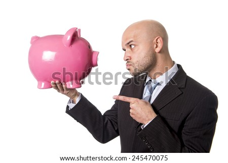 businessman holding piggybank face to face pointing the piggy bank with his finger as a you better be full of money warning isolated on white background - stock photo