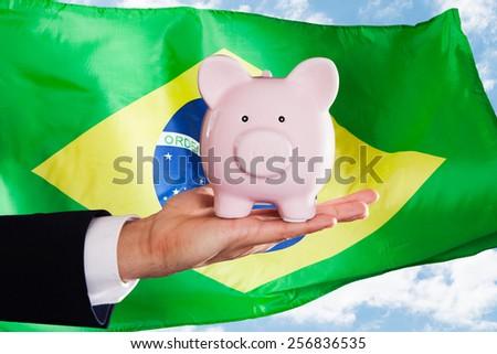 Businessman Holding Piggybank In Front Of Brazilian Flag - stock photo