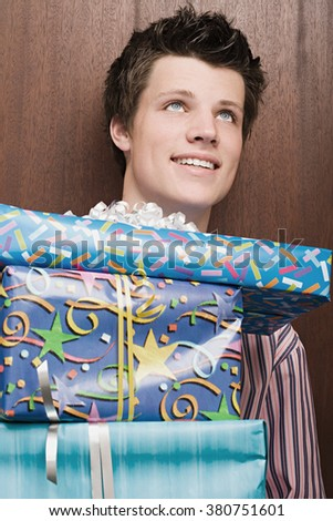 Businessman holding pile of presents - stock photo