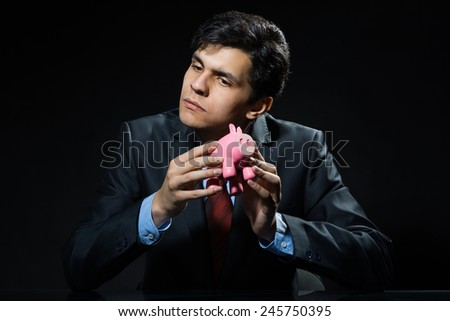 Businessman holding pink piggy bank in hands
