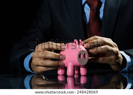 Businessman holding pink piggy bank in hands - stock photo