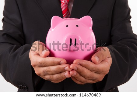 Businessman holding pink piggy bank, isolated on white background.