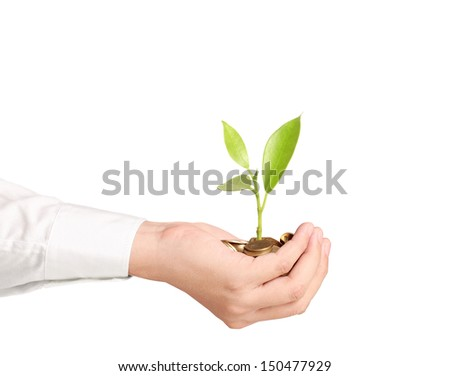 Businessman holding plant sprouting from a handful of coins