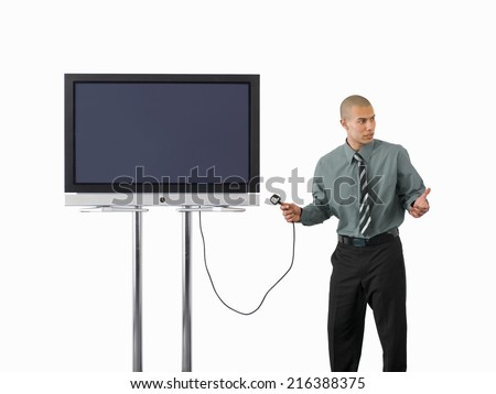 Businessman holding plug to widescreen television, cut out