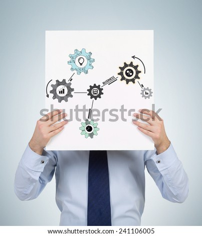 businessman holding poster with drawing cogs and gears - stock photo