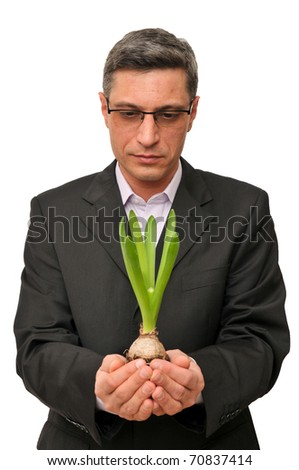 Businessman holding protective small plant