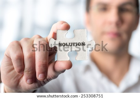 Businessman holding puzzle piece with word Solution in a conceptual image for successfully overcoming problems and challenges. - stock photo