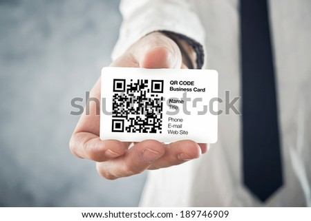Businessman holding QR code business card with personal data. Modern technology concept. - stock photo