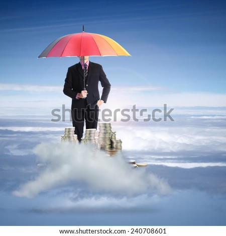 Businessman holding rainbow umbrella for protect his finance on the cloud - stock photo