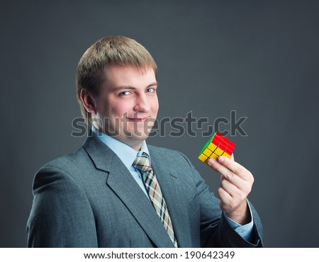 Businessman holding rubik cube in his hands - stock photo