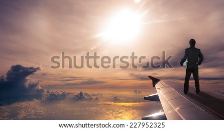 businessman holding safety helmet standing on airplane wing, successful business concept - stock photo