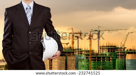 Businessman holding safety helmet with construction site in background - stock photo