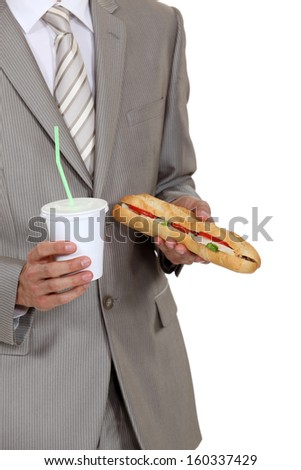 Businessman holding sandwich and soft drink - stock photo