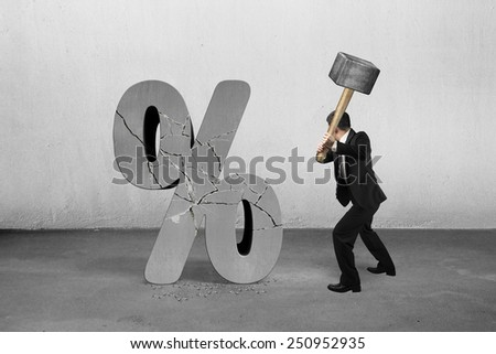 Businessman holding sledgehammer hitting cracked percentage sign with concrete room background - stock photo