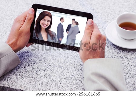 Businessman holding small tablet at table against happy businesswoman posing while her team discussing - stock photo
