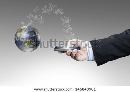 Businessman holding smart phone sending email to globe. Data source: Nasa - stock photo