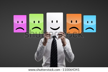 businessman holding smilies  on a black background - stock photo