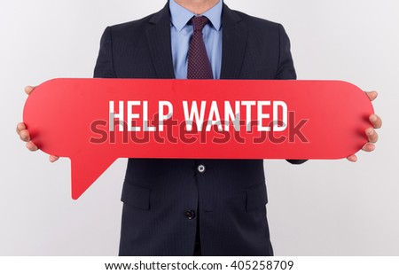 Businessman holding speech bubble with a word HELP WANTED - stock photo