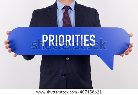 Businessman holding speech bubble with a word PRIORITIES - stock photo