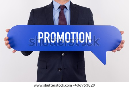 Businessman holding speech bubble with a word PROMOTION - stock photo